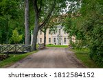 Rural road leads to the old manor in Eclectic style. Gravel path street with green trees in summer.  - stock photo