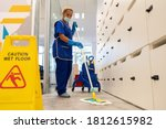 Small photo of A cleaner with a mask on her face cleans the floor with the mop.Caution wet floor sign close up