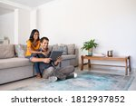 Small photo of Young middle eastern couple using digital tablet while sitting on couch and floor. Happy smiling indian woman embracing from behind her boyfriend while watching video on digital tablet at home.