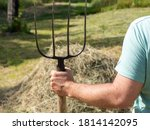 A Man Is Holding A Pitchfork....