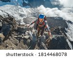 Small photo of Climber in a safety helmet, harness with backpack ascending a rock wall with Bionnassay Glacier on background and looking at the summit during Mont Blanc ascending,France route.Active climbing concept