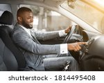 Small photo of African american man in suit driver turning on music in car before moving. Cheerful black businessman pushing button on functional panel in his car, turning on music before starting business trip