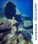 """Small photo of The statue of """" Madonna del Naufrago """" under the water in the protect area of Capo Carbonara in Villasimius. Madonna with child statue underwater. Madonna of castaway."""