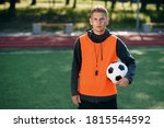 Small photo of Confident professional soccer coach in an orange vest and a whistle on neck at artificial football field at morning.