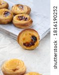 Small photo of Traditional Portuguese popular dessert Pastel de nata or Pastel de Belem. Delicious puff pastry cups with custard. Vertical orientation.