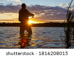 Silhouette of angler catching the fish durring sunset with lens flare defect.