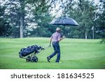 Golfer On A Rainy Day Leaving...