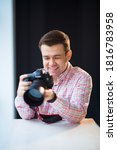 a male photographer in a checkered shirt sits at a table and holds a camera in his hands. creative profession or hobby. professional photo sessions. - stock photo