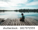 Boy Sitting Alone On Pier While ...