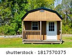 Small photo of American style wooded shed, with porch. A shed is typically simple, single-story roofed structure in a back garden or on an allotment that is used for storage, hobbies, or as a workshop. Exterior view