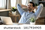 Small photo of Calm millennial man in glasses sit relax at home office workplace take nap or daydream. Happy relaxed Caucasian young male rest in chair distracted from computer work, relieve negative emotions.