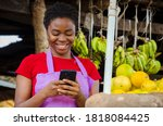 Small photo of a young beautiful african market woman feeling happy about what she saw on her cellphone