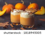 Small photo of Pumpkin latte drink. Autumn coffee with spicy pumpkin flavor and cream on a dark background. Seasonal Fall Drinks for Halloween and Thanksgiving