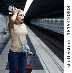 Small photo of Portrait of disquieted young woman standing on subway station platform