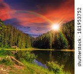 view on lake with rainbow near the pine forest  on mountain background at sunset - stock photo