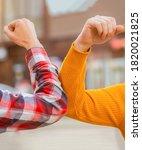 Small photo of Friends shaking elbows outdoors. Elbow greeting style. Coronavirus epidemic. Coronavirus, illness, infection, quarantine, COVID-19. Don't shake hands. Stop handshakes.