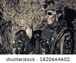 Smiling US army soldier, SEALs fighter, modern combatant in combat uniform, plate carrier, ballistic glasses and battle helmet resting after fight, sitting in trench at night and smoking cigarette - stock photo