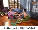 Small photo of Asian women wearing Thai traditional dresses cooking Thai traditional food in the Thai ancient house Ayutthaya,Thailand