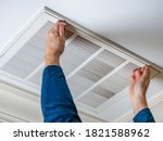 Man Opening Ceiling Air Vent To ...