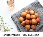 Small photo of A bowl of Lokma (Turkish), loukoumades (Greeek ) with other names in other languages, are pastries made of leavened and deep fried dough, soaked in syrup or honey, sometimes coated with cinnamon