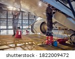 Small photo of Full length side view portrait of men aviation mechanics fixing and checking spoiler and flaps on the airplane