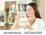 Happy Woman Eating Cereals For...