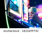 Slot Machine Play Time. Female Gambler Hand hold money bill ready to win the game with one best shot casino close up - stock photo