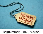 Small photo of Small Business Saturday sign - a paper price tag with a twine against blue paper background, local holiday shopping concept