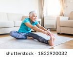 Small photo of senior woman doing warmup workout at home. Fitness woman doing stretch exercise stretching her legs,quadriceps .Elderly woman living an active lifestyle.
