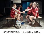 Small photo of Kid's soccer team building up togetherness in a locker room