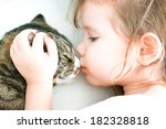 Cute Baby Girl Is Kissing A Cat