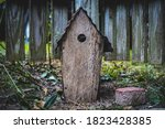 Small photo of Strange abandoned wooden birdhouse with unsettling overtones abound