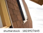 Small photo of Roofing construction and building new house with skylights, new brick house with chimney. Modern Roof Skylight. Attic Skylights Home Design. Roofing Construction. Clay Roof Tiles