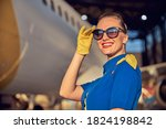 Small photo of Close up portrait of happy smiling female air hostess posing at the photo camera in front of passenger aircraft