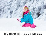 Kid Making Snowman In Snowy...