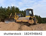 Dozer and Vibro Roller Soil Compactor at road construction and bridge projects in forest area. Heavy machinery for road work. Building a road works.  - stock photo