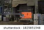Small photo of Loader mixing red-hot aluminium in bowl in aluminium plant. Aluminium foundry furnace loaded with metal. Red hot flames glowing and liquid melting. Fire melts aluminum ingots in a blast furnace.