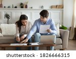 Small photo of Payday. Concentrated attentive millennial spouses sitting on couch at home discussing possibility of taking out loan or credit, counting sum of taxes or bills to pay online using laptop and calculator
