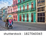 Small photo of A tricycle taxi riding along beautiful colourful buildings in Havana Cuba