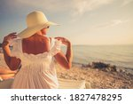 Retired Caucasian Woman Wearing Sun Protection Hat Relaxing on a Beach Seating on White Plastic Deck Chair. Vacation Time Theme. - stock photo