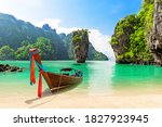 Small photo of Famous James Bond island near Phuket in Thailand. Travel photo of James Bond island with thai traditional wooden longtail boat and beautiful sand beach in Phang Nga bay, Thailand.