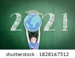 Small photo of 2021 new educational academic calendar year for school class with student kid raising world global planet on teacher's green chalkboard for back to school celebration, classroom schedule concept