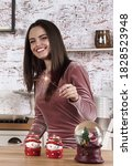 Small photo of Young Brunette woman holding sparker stick and celebrating new year at home
