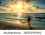Small photo of Seascape at sunrise with beautiful sky. Woman on the beach. Young happy woman in a yellow fluttering dress walks along the seashore. The girl looks at the magical sunrise. Seagulls fly over the beach