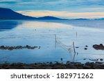 Reflective Beach With A Fishin...