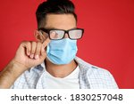 Man wiping foggy glasses caused by wearing medical mask on red background