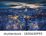 Winter evening sunset with snowy and illuminated buildings, Rosengarten, Bern, UNESCO, Switzerland
