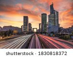 Long exposure sunset on the multinational headquarters and finance institutions in La Defense, Paris business district with car and metro tramway light beams