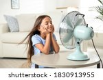 Small photo of Little girl enjoying air flow from fan at home. Summer heat