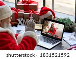 Small photo of Over shoulder view of Santa Claus video calling kid girl on laptop greeting child by webcam talk open Christmas gift box in virtual online chat meeting using computer sit at workshop table on xmas.
